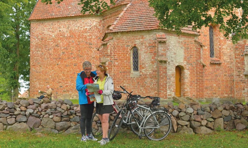 Fahrradfahrer vor der Kirche in Ludorf, Mecklenburgische Seenplatte
